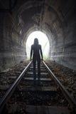 Mens in een tunnel die naar het licht kijken Stock Fotografie