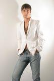 Mens in een wit jasje en jeans Royalty-vrije Stock Foto's