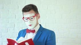 Mens in een wit masker die een boek lezen stock videobeelden
