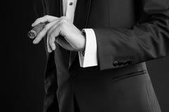 Mens in een zwart kostuum met een sigaar Stock Foto's