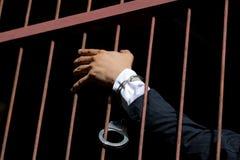 Mens in een zwart kostuum met handcuffs op zijn handen op donkerblauwe B Royalty-vrije Stock Foto