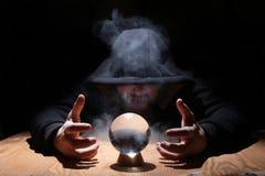 Mens in een zwarte kap met cristal bal stock afbeelding