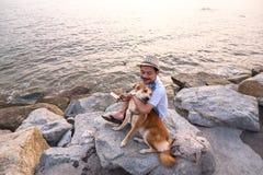 Mens en een hondzitting samen op de steen dichtbij het overzees royalty-vrije stock fotografie