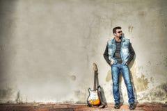 Mens en gitaar die op de muur leunen royalty-vrije stock afbeeldingen
