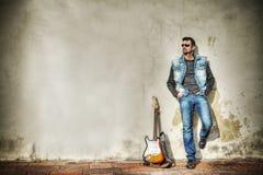 Mens en gitaar tegen een grungy muur in hdr Stock Foto