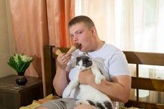 Mens en grappige kat die roomijskegel in het bed eten Royalty-vrije Stock Foto