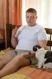 Mens en grappige kat die roomijskegel in het bed eten Stock Afbeelding