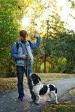 Mens en hond in de herfstpark stock afbeelding
