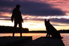 Mens en hond die op de zonsondergang letten Stock Fotografie