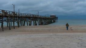 Mens en hond die op strand op stormachtige dag lopen royalty-vrije stock foto