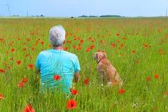 Mens en hond op poppiegebied stock fotografie
