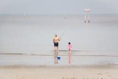 Mens en jong geitje die naar het overzees aan vissen lopen Royalty-vrije Stock Afbeeldingen