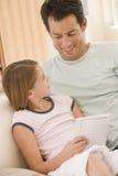 Mens en jong meisje in het boek van de woonkamerlezing Royalty-vrije Stock Afbeelding