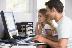 Mens en jong meisje in huisbureau met computer Royalty-vrije Stock Foto's