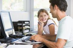 Mens en jong meisje in huisbureau met computer Stock Foto