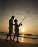 Mens en jonge jongen die in branding vissen Royalty-vrije Stock Foto