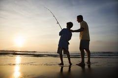 Mens en jonge jongen die in branding vissen Stock Foto