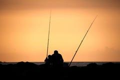 Mens en jonge jongen die in branding vissen Royalty-vrije Stock Afbeeldingen