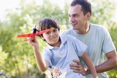 Mens en jonge jongen die in openlucht met stuk speelgoed vliegtuig spelen Royalty-vrije Stock Afbeeldingen
