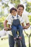 Mens en jonge jongen op een fiets die in openlucht glimlacht stock foto