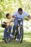 Mens en jonge jongen op fietsen die in openlucht glimlachen Royalty-vrije Stock Foto's