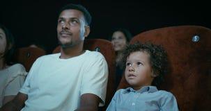 Mens en jongen bij de films stock video