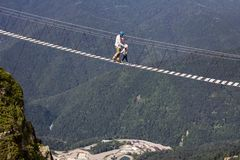 Mens en jongen in de bergen op een extreme gang stock fotografie