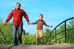 Mens en jongen die op brug in de zomer in werking wordt gesteld stock afbeelding