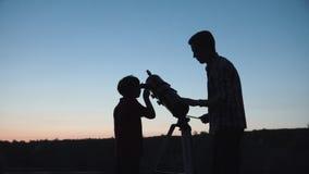 Mens en jongen die telescoop gebruiken royalty-vrije stock afbeeldingen