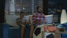 Mens en jongens het spelen videospelletje samen stock video