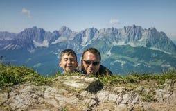 Mens en jongens het verbergen Kitzbuhelpiek, Oostenrijk Stock Afbeeldingen