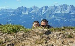 Mens en jongens het verbergen Kitzbuhelpiek, Oostenrijk Royalty-vrije Stock Afbeeldingen