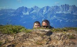 Mens en jongens het verbergen Kitzbuhelpiek, Oostenrijk Stock Fotografie