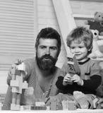 Mens en jongensspel met stuk speelgoed kanon op houten muurachtergrond De vader en de zoon met gelukkige gezichten creëren kleurr Stock Foto's