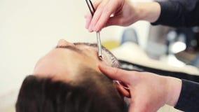 Mens en kapper met rechte scheermes het scheren baard stock footage