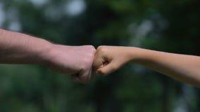 Mens en kindponsenvuisten, ouders als betrouwbare steun voor kinderen, close-up stock videobeelden