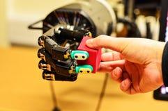 Mens en Mechanische Hand die een Rode Kubus in het Onderzoeklaboratorium houden royalty-vrije stock foto's