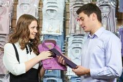 Mens en medewerker bij kledingskleren het winkelen stock afbeelding