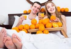 Mens en meisje die gedrukt jus d'orange in bed drinken stock afbeeldingen