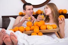 Mens en meisje die gedrukt jus d'orange in bed drinken royalty-vrije stock afbeelding