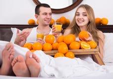 Mens en meisje die gedrukt jus d'orange in bed drinken royalty-vrije stock foto's