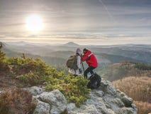 Mens en meisje die zonsondergang op de hoogste berg schieten stock foto