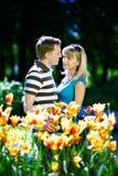 Mens en meisje onder bloemen Stock Foto
