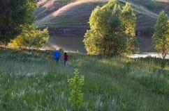 Mens en meisje op de groene kust van het meer royalty-vrije stock afbeelding