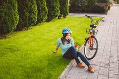 Mens en stads rollende fiets, milieuvriendelijk vervoer De mooie jonge Kaukasische zitting die van de vrouwenarbeider op gr. rust royalty-vrije stock foto