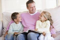 Mens en twee kinderen die in woonkamer zitten Royalty-vrije Stock Foto's