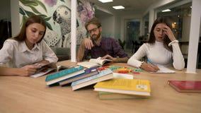 Mens en twee meisjes die in moderne atr koffiezitting bij de lijst met dicht omhoog boeken bestuderen stock videobeelden