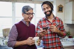 Mens en Vader Looking in Smartphone samen royalty-vrije stock afbeeldingen