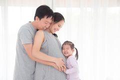 Mens en zijn dochter die zwangere vrouw en glimlach koesteren royalty-vrije stock afbeeldingen
