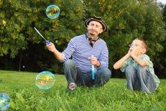 Mens en zoon die zeepbel bekijken Stock Foto's